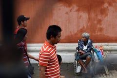 De mensen gaan door Etnische oude vrouwenzitting over op de doos van de Kerstmisgift van de rolstoelholding bedelend voor aalmoes royalty-vrije stock fotografie