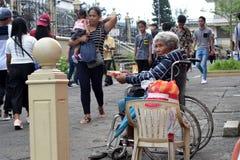 De mensen gaan door Etnische oude vrouwenzitting over op de doos van de Kerstmisgift van de rolstoelholding bedelend voor aalmoes royalty-vrije stock afbeeldingen