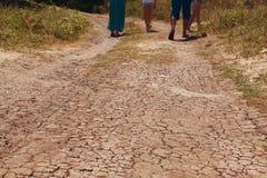 De mensen gaan langs de droge weg in barsten op plattelandsgebieden met uitgedroogd klimaat stock afbeelding