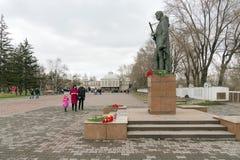 De mensen gaan naar het Alesha-monument naar militairen van WO.II op de achtergrond van Victory Memorial in de Krasnoyarsk-stad stock foto's