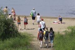 De mensen gaan naar het strand zonnebaden stock afbeeldingen
