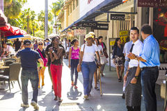 De mensen gaan winkelend in de middagzon in Lincoln Road Stock Afbeeldingen