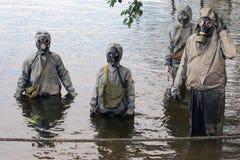 De mensen in gasmaskers bewegen zich op de rivier voor verdedigingsteachi Stock Foto's