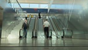 De mensen gebruiken een roltrap in luchthaventerminal of bij de wandelgalerij De mensen` s gezichten zijn niet te onderscheiden stock video