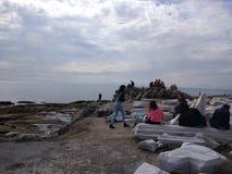 De mensen genieten van lopend door Antalya-Kant op het strand in een zonnige dag stock afbeelding
