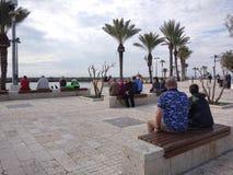 De mensen genieten van lopend door Antalya-Kant op het strand in een zonnige dag stock afbeeldingen