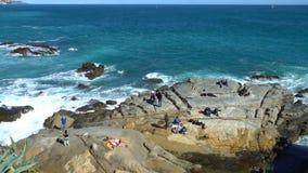 De mensen genieten van de zon en de golven op de kustklippen stock video