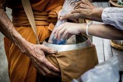 De mensen geven aalmoesvoedsel en punt die aan Boeddhistische monnik aanbieden Royalty-vrije Stock Foto
