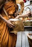 De mensen geven aalmoesvoedsel en punt die aan Boeddhistische monnik aanbieden Stock Afbeelding