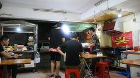 De mensen geven opdracht tot voedsel dat en het eten van vlees met de peper van Sichuan bij restaurant wordt geroosterd stock footage