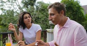 De mensen groeperen het Spreken Etend Voedsel op Terras Jonge Vrienden die bij Lijst in openlucht Mededeling zitten stock videobeelden