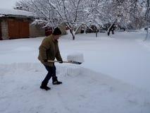 De mensen halen de sneeuwschoppen na zware sneeuwval weg stock foto