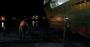 De mensen, havenarbeiders, hulp leggen een commercieel schip vast stock videobeelden