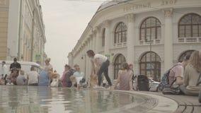 De mensen hebben een rust rond de fontein dichtbij Gostinniy Dvor in Moskou stock video