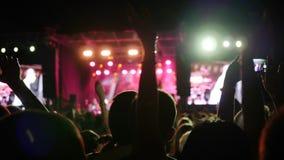 De mensen heffen wapens op en juichen musici in heldere brand van stadium toe, overbevolken klap van handen en de rotsfestival va stock videobeelden