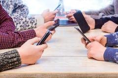 De mensen in het bureau houden smartphones in hun handen De jongeren hebt pret met smartphones Spelen op mobiele phones_ royalty-vrije stock foto's