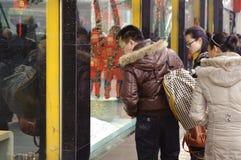 De mensen houden om in het venster van een gouden winkel te kijken op Royalty-vrije Stock Foto's