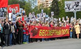 De mensen houden rode banner van Onsterfelijk regiment en portretten van hun verwanten op 9 Mei, 2016 in Ulyanovsk, Rusland Stock Afbeeldingen