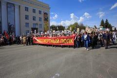 De mensen houden rode banner van Onsterfelijk regiment en portretten van hun verwanten op 9 Mei, 2016 in Ulyanovsk, Rusland Stock Fotografie