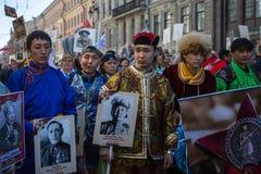 De mensen houden vlaggen en beelden van Wereldoorlog Twee militairen aangezien zij aan het Onsterfelijke Regiment maart deelnemen Stock Afbeeldingen