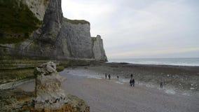 De mensen inspecteren at low tide naakt strand Bewolkte de winterdag in Etretat frankrijk stock footage
