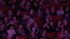 De mensen juichen in de bioscoop toe stock footage