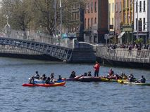 De mensen in Kano's door de Stuiver van Ha ` overbruggen over Rivier Liffey in de stad van Dublin, Ierland royalty-vrije stock afbeeldingen