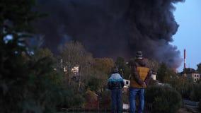De mensen kijken als een huis branden De tragedie, mensen bekijkt een vuurzee in de stad Narigheid van mensen onderaan worden geb stock footage