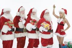 De mensen kleedden zich in Santa Claus Outfits With Mrs. Claus Holding Mistletoe royalty-vrije stock foto's