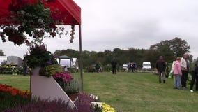 De mensen kopen bloemen en installaties in botanische festivalmarkt stock video