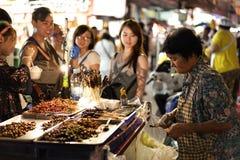 De mensen kopen gebraden insecten in Yaowarat stock afbeelding
