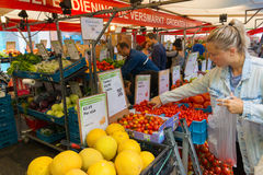 De mensen kopen groenten bij de markt stock foto's