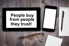 De mensen kopen van mensen die zij hebben vertrouwd op! Tekst op tabletapparaat royalty-vrije stock fotografie