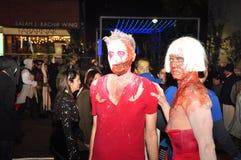 De mensen in kostuums bij Zombie lopen en paraderen Stock Afbeelding