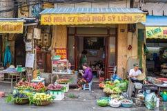 De mensen kunnen gezien hebbend hun voedsel naast de straat en diverse types van vruchten die van de traditionele hangende manden Royalty-vrije Stock Foto