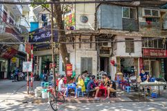 De mensen kunnen gezien hebbend hun voedsel naast de straat in de ochtend in Hanoi, Vietnam Royalty-vrije Stock Foto's