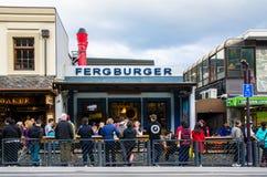 De mensen kunnen het gezien een rij vormen van en het wachten van hun voedsel voor het restaurant van Fergburger in Queenstown Stock Fotografie