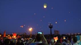 De mensen lanceren luchtlantaarns bij nacht stock footage