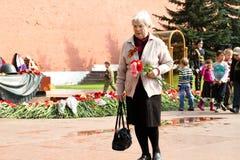 De mensen leggen bloemen bij de Eeuwige vlam in Aleksandrovsk aan een tuin in Victory Day Royalty-vrije Stock Foto