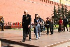 De mensen leggen bloemen bij de Eeuwige vlam in Aleksandrovsk aan een tuin in Victory Day Royalty-vrije Stock Afbeelding
