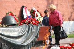 De mensen leggen bloemen bij de Eeuwige vlam in Aleksandrovsk aan een tuin in Victory Day Royalty-vrije Stock Afbeeldingen