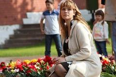 De mensen leggen bloemen bij de Eeuwige vlam in Aleksandrovsk aan een tuin in Victory Day Stock Fotografie