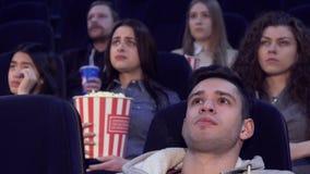 De mensen letten op ernstige film bij de bioscoop stock videobeelden