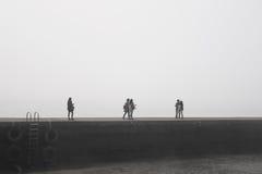 De mensen liepen doelloos met geheimzinnige mist op de steiger bij haven royalty-vrije stock afbeeldingen