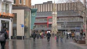 De mensen lopen binnen de stad in in een bewolkte ochtend Winkels op achtergrond stock videobeelden