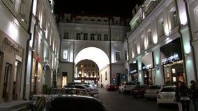 De mensen lopen dichtbij winkels en boutiques in Moskou bij nacht stock video