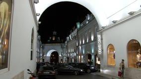 De mensen lopen dichtbij winkels en boutiques in Moskou bij nacht stock videobeelden