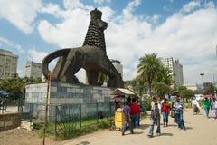 De mensen lopen door de straat naast het iconische standbeeld van de Leeuw van Judah in Addis Ababa, Ethiopië Stock Foto