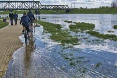 De mensen lopen en berijden langs overstroomde boulevards lettend op de rivier tijdens de de lentevloed van water stock foto's