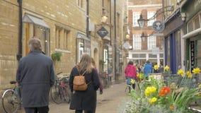 De mensen lopen langs de charmante oude straat in het centrum van Cambridge stock video